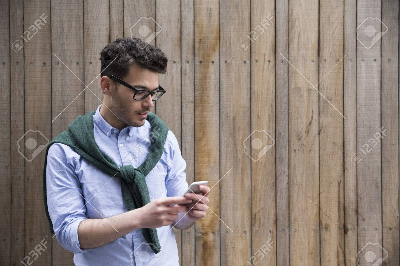 Portrait of young man using a smart phone outdoors. Stock Photo - 44404352