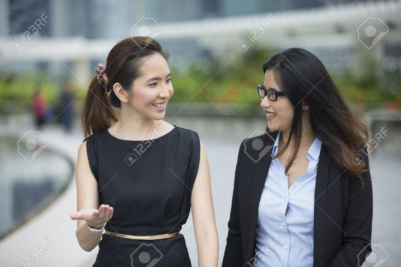 Happy Chinese Business women walking outside office & talking to each other. Stock Photo - 54491180