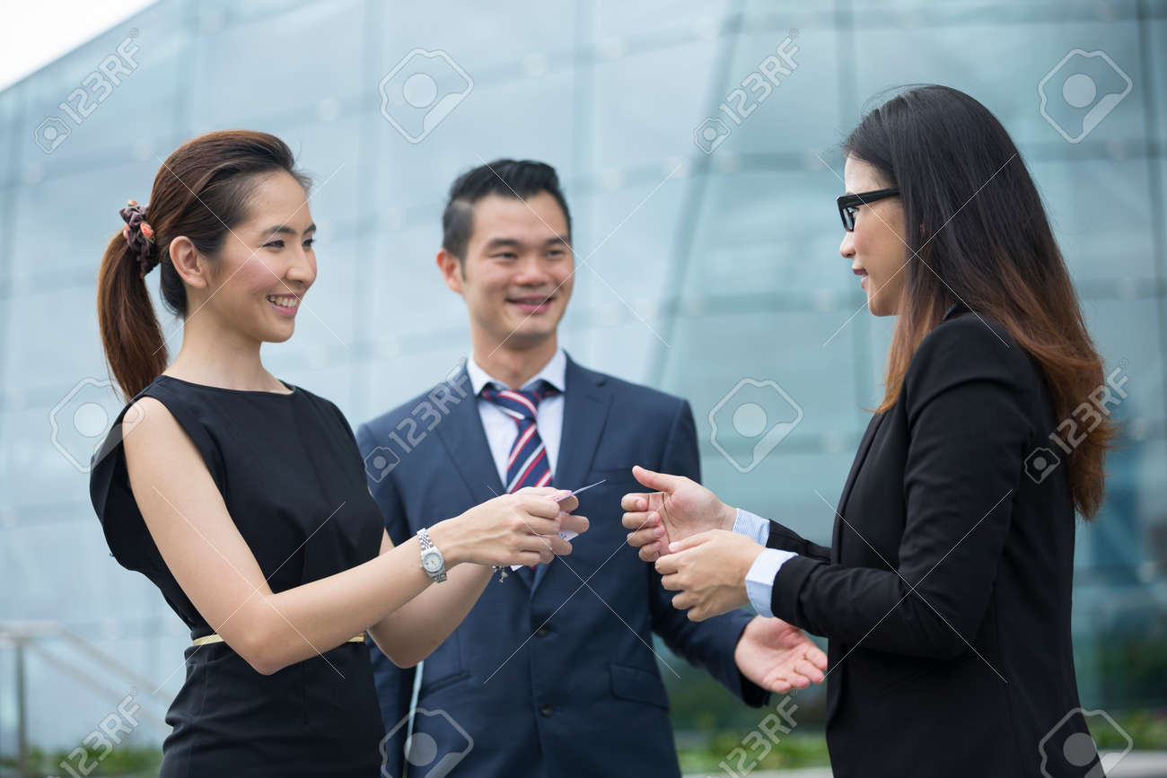 Asian Businesswoman presenting her business card to a female business collegue. Stock Photo - 54492175