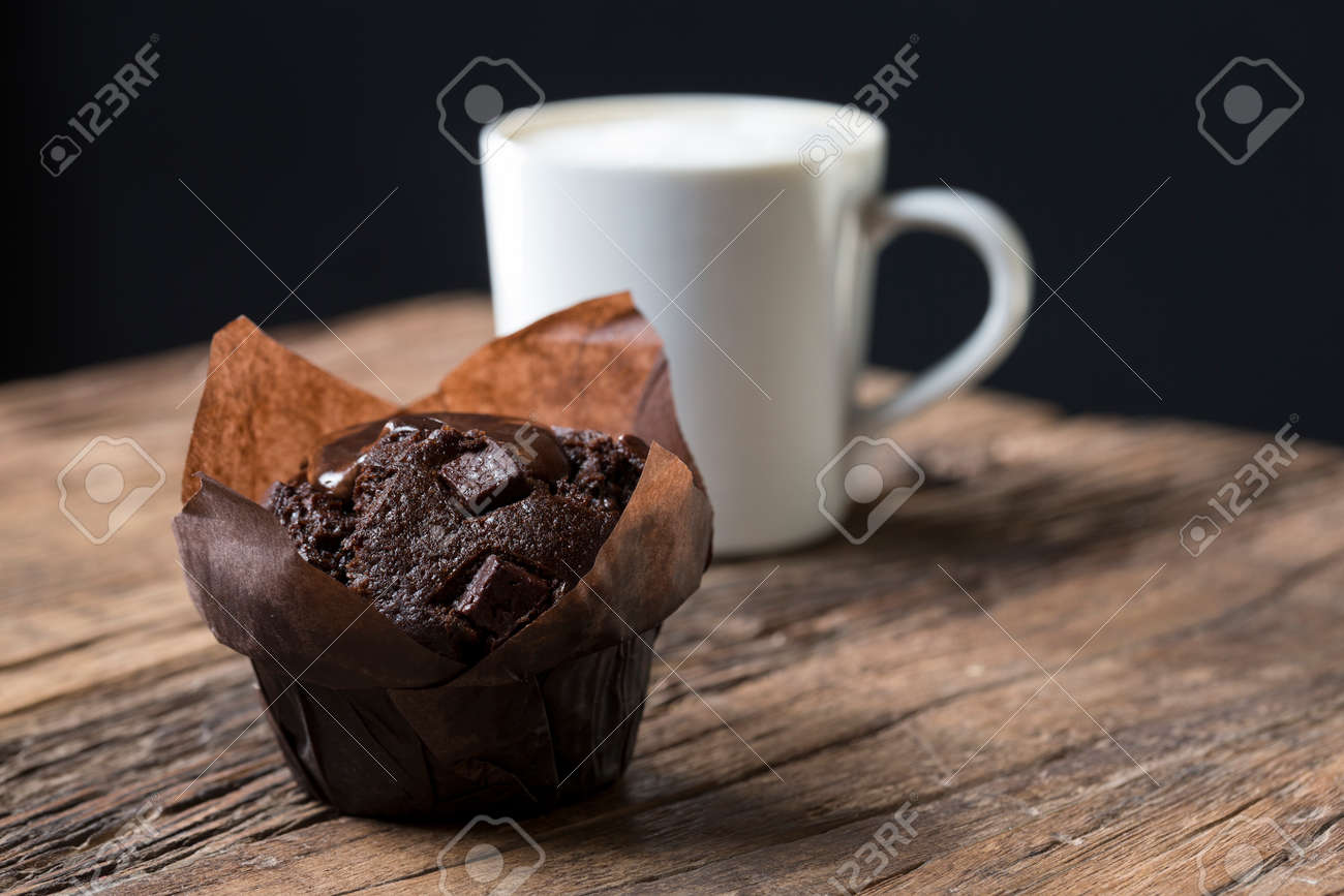 A freshly baked Chocolate Muffin and a Cappuccino coffee, sitting on an old rustic, wooden table. Stock Photo - 54597310