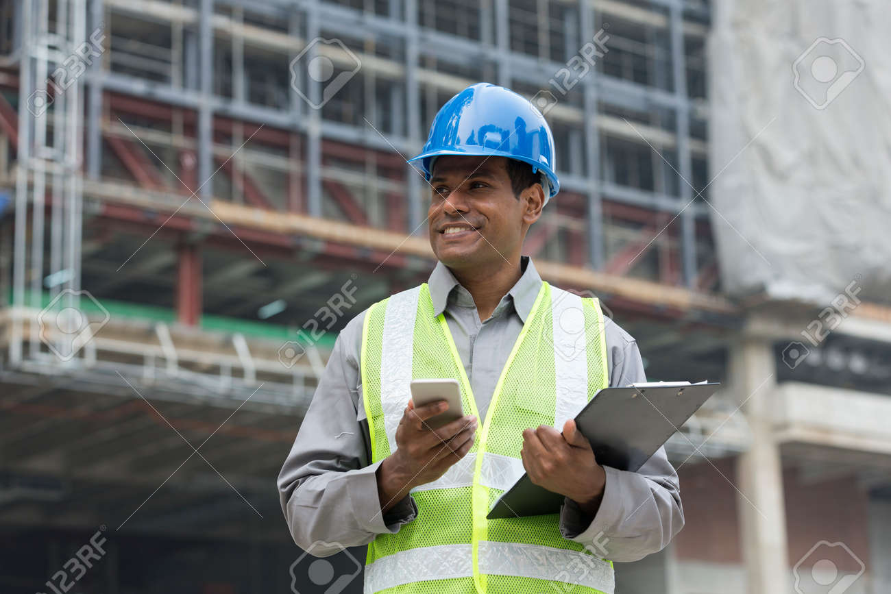 Portrait of a male Indian builder or industrial engineer at work using phone. - 54598372