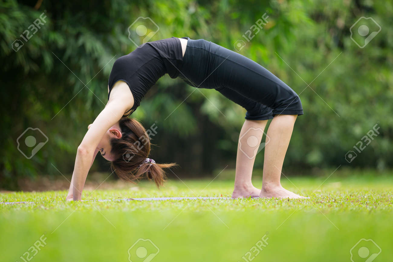 Asian Woman Wearing Black Clothes, Practicing Yoga In A Garden ...