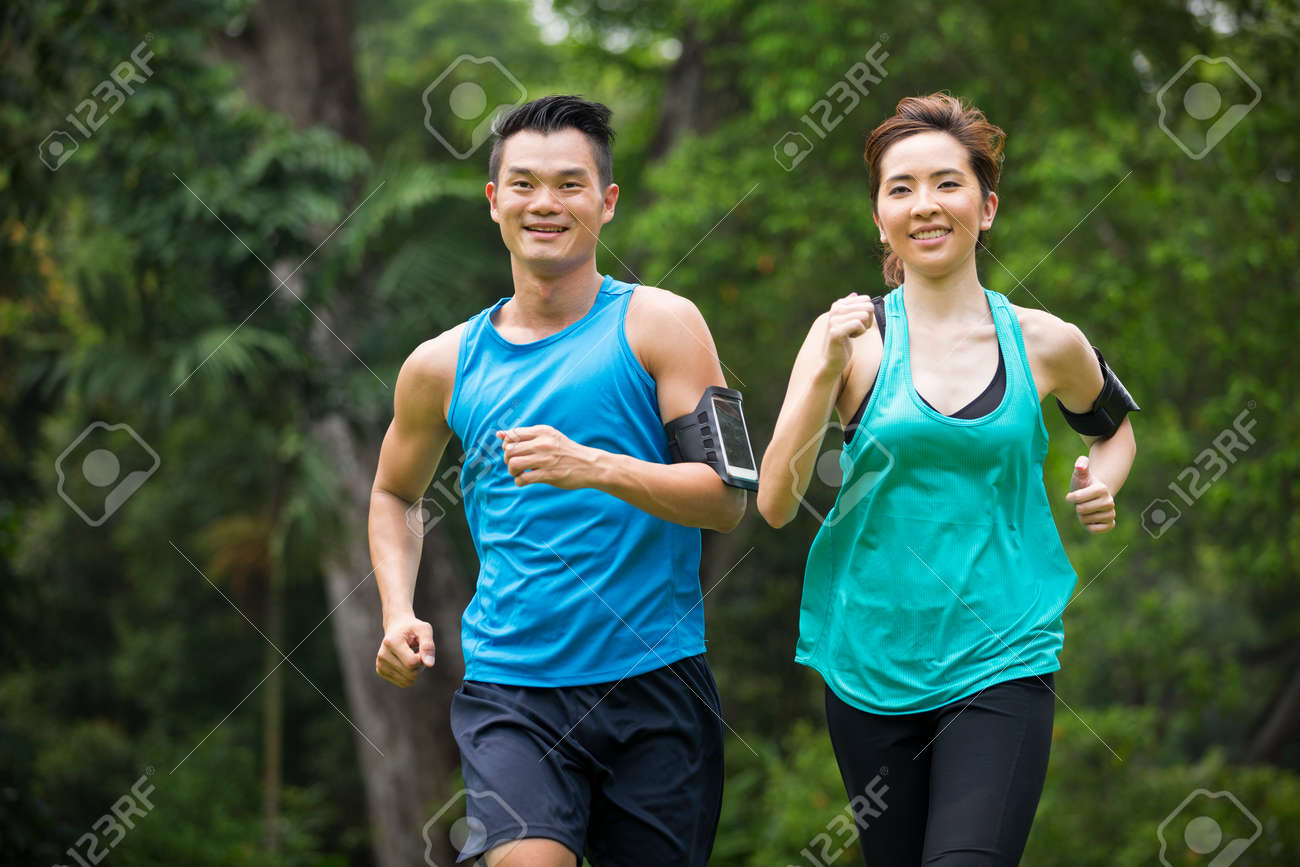 Athletic Asian man and woman running outdoors. Action and healthy lifestyle concept. Stock Photo - 57349557