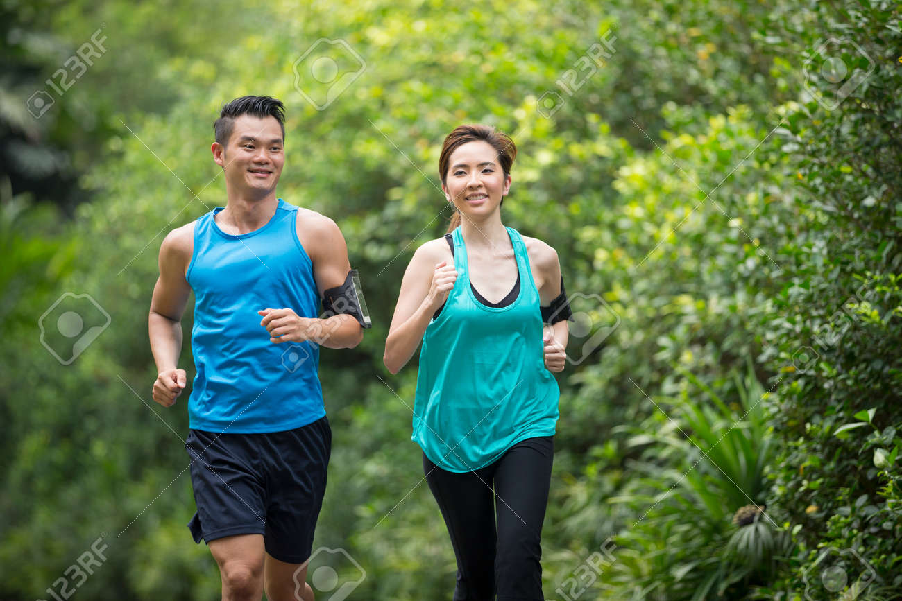 Athletic Asian man and woman running outdoors. Action and healthy lifestyle concept. Stock Photo - 57309295