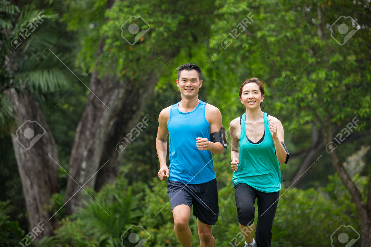 Athletic Asian man and woman running outdoors. Action and healthy lifestyle concept. Banque d'images - 57309106