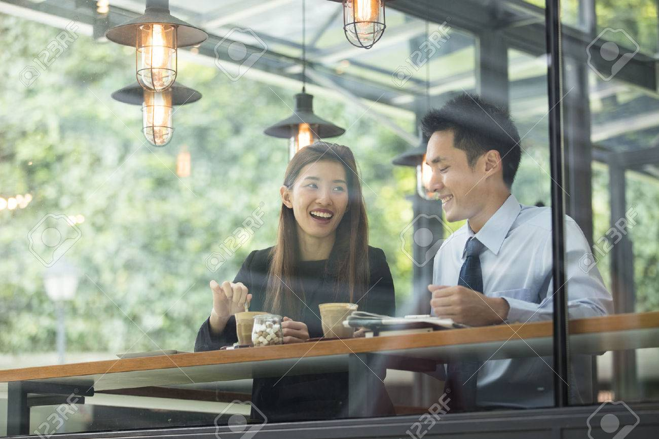 Asian business man and woman meeting in a coffee shop. Stock Photo - 65991963