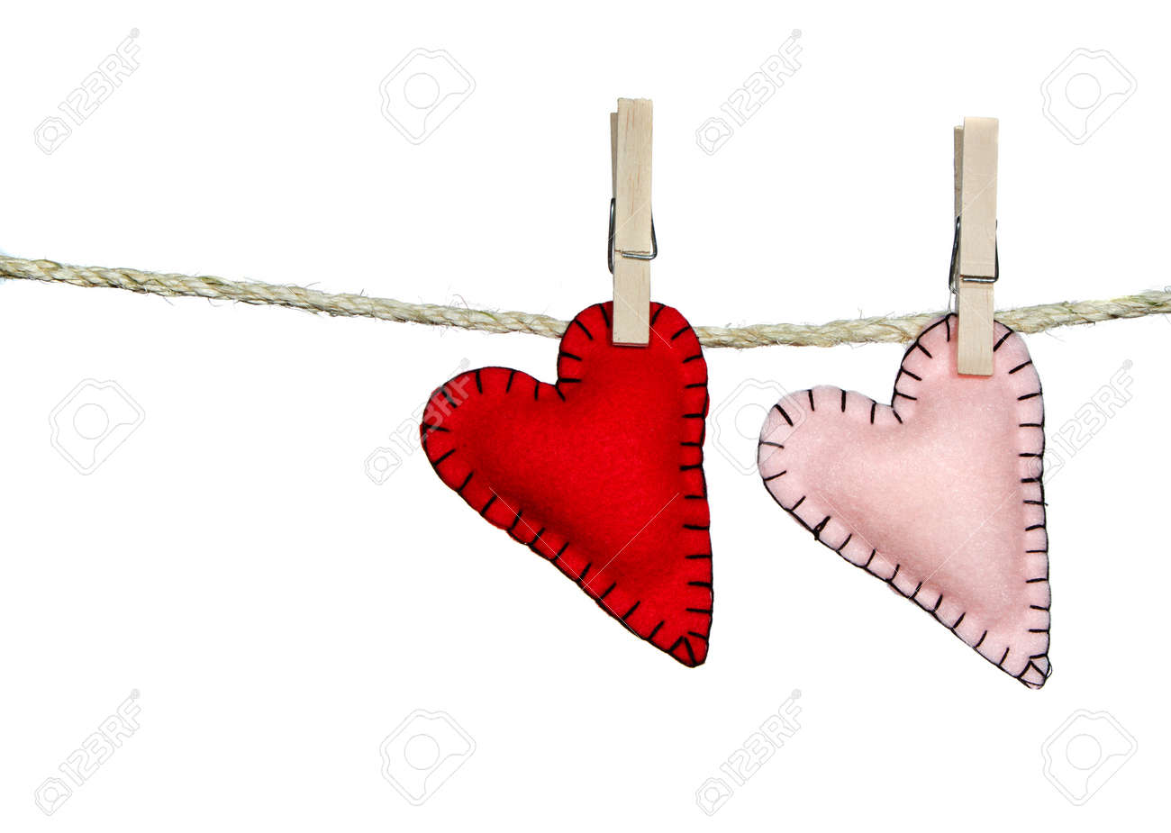 Two stiched valentine hearts pink and red on a clothes line. They are handmade out of felt. Isolated on a white background Stock Photo - 12157506
