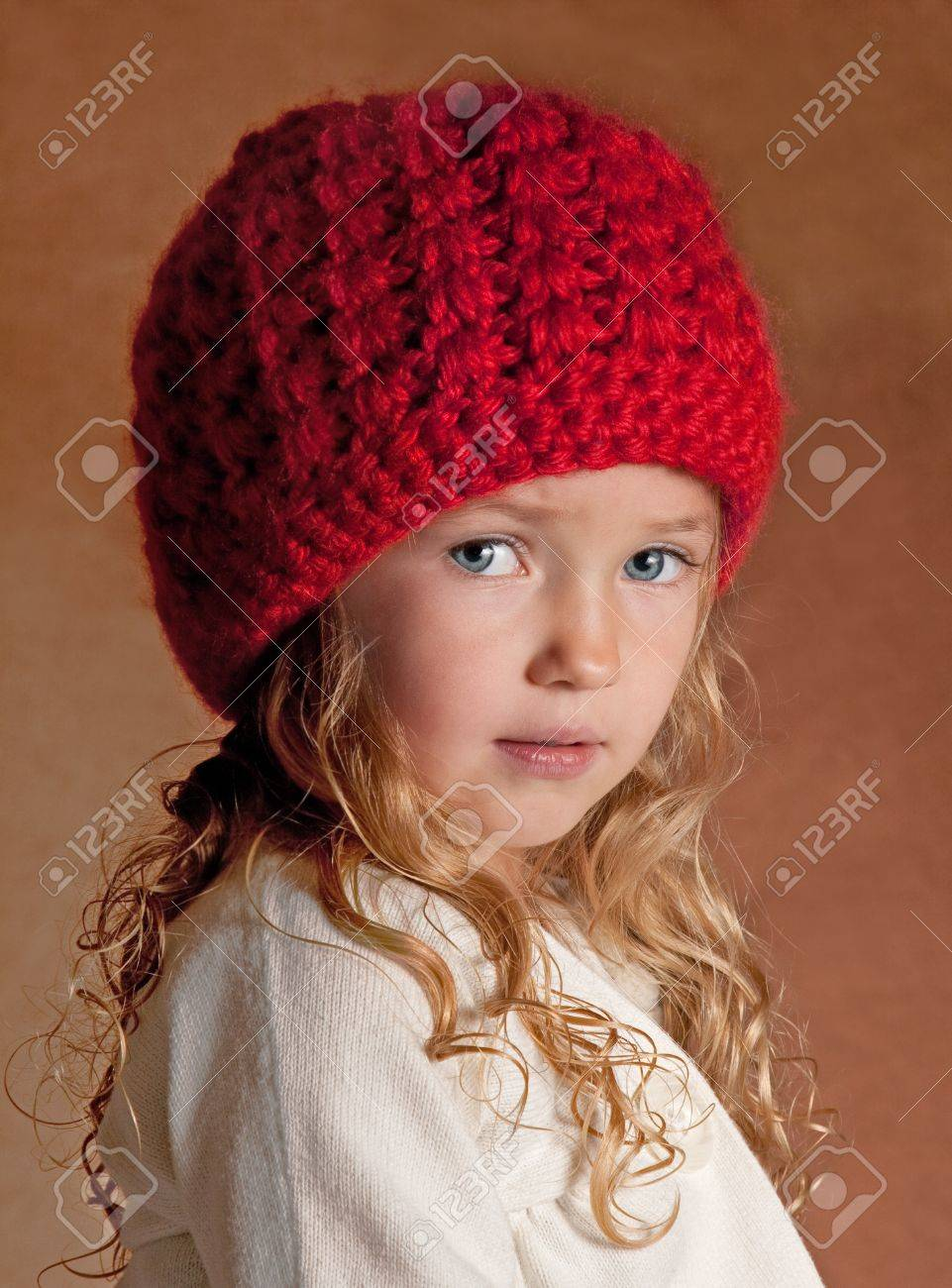 fa5190f8c25 a cute girl wearing a red knit winter hat and a red knit scarf. portrait
