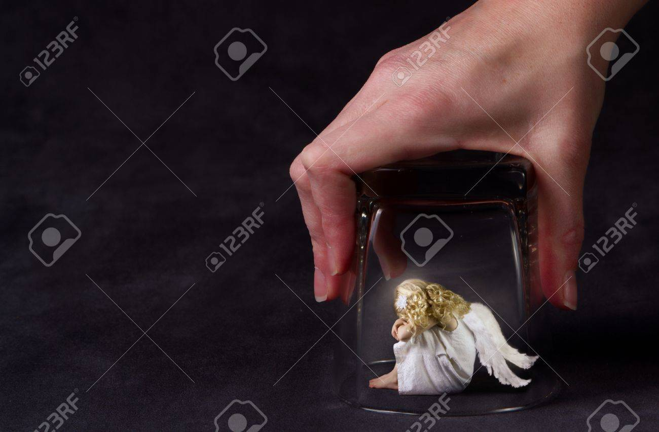 An angel trapped under a glass, a child angel or fallen angel Stock Photo - 12892979