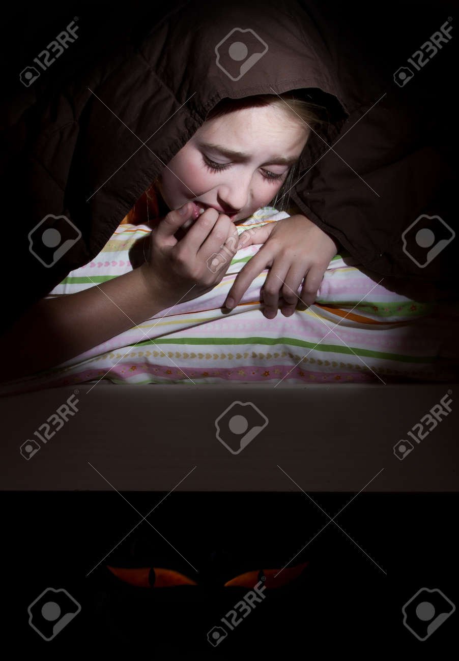 Girl scared in her bed at nighttime imagining monsters under bed Stock Photo - 14416867