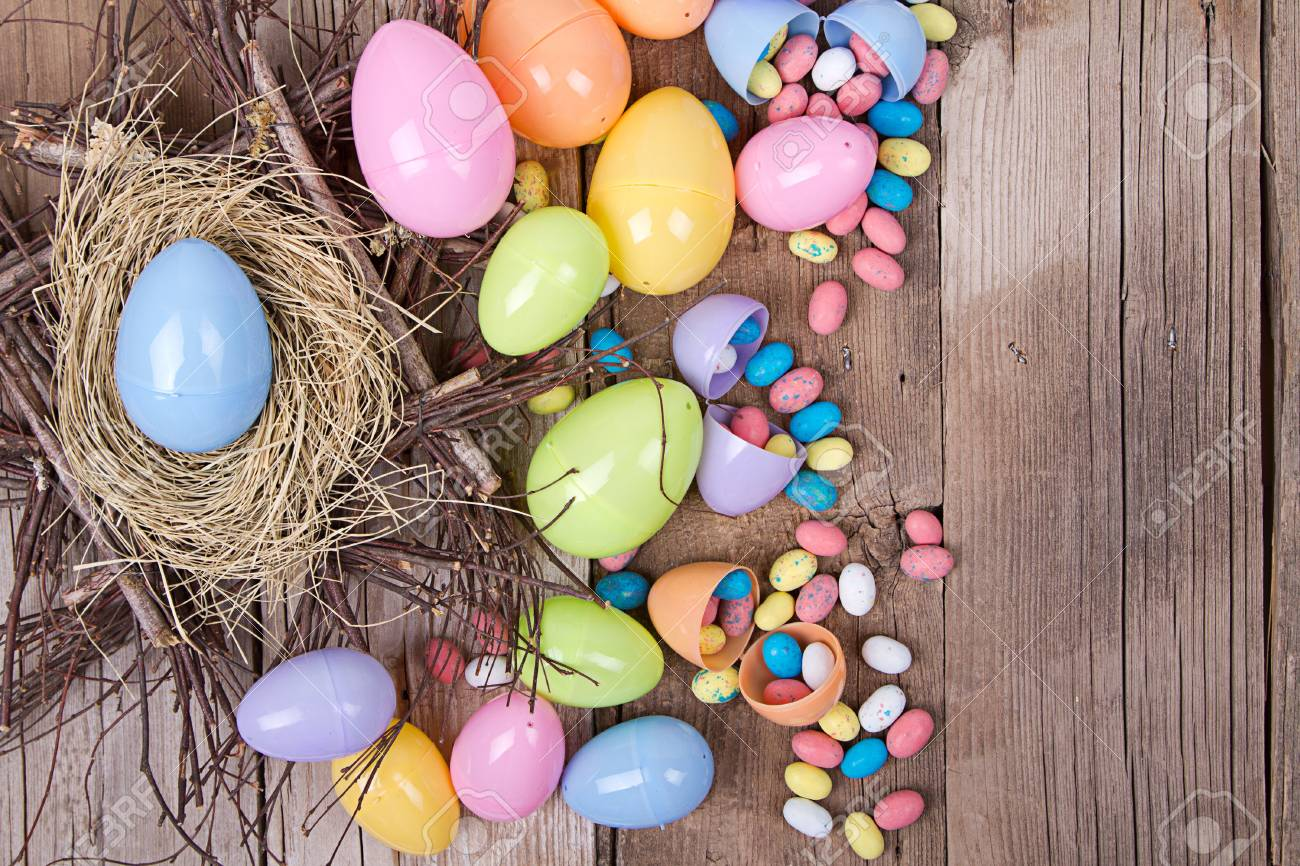 Plastic Easter Eggs By Nest Filled With Candy On A Wooden Background Stock Photo