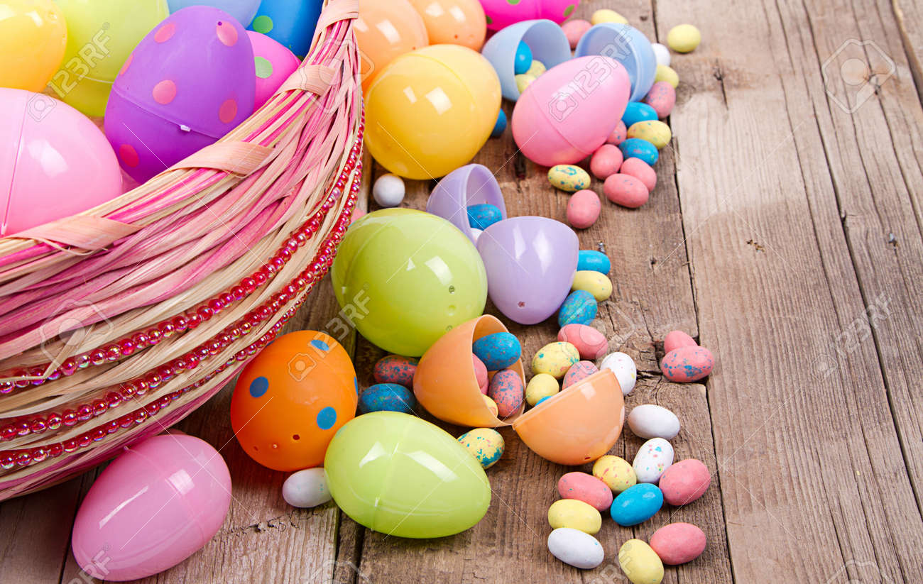 Plastic Easter Eggs Filled With Candy In A Basket On Wooden Background Stock Photo