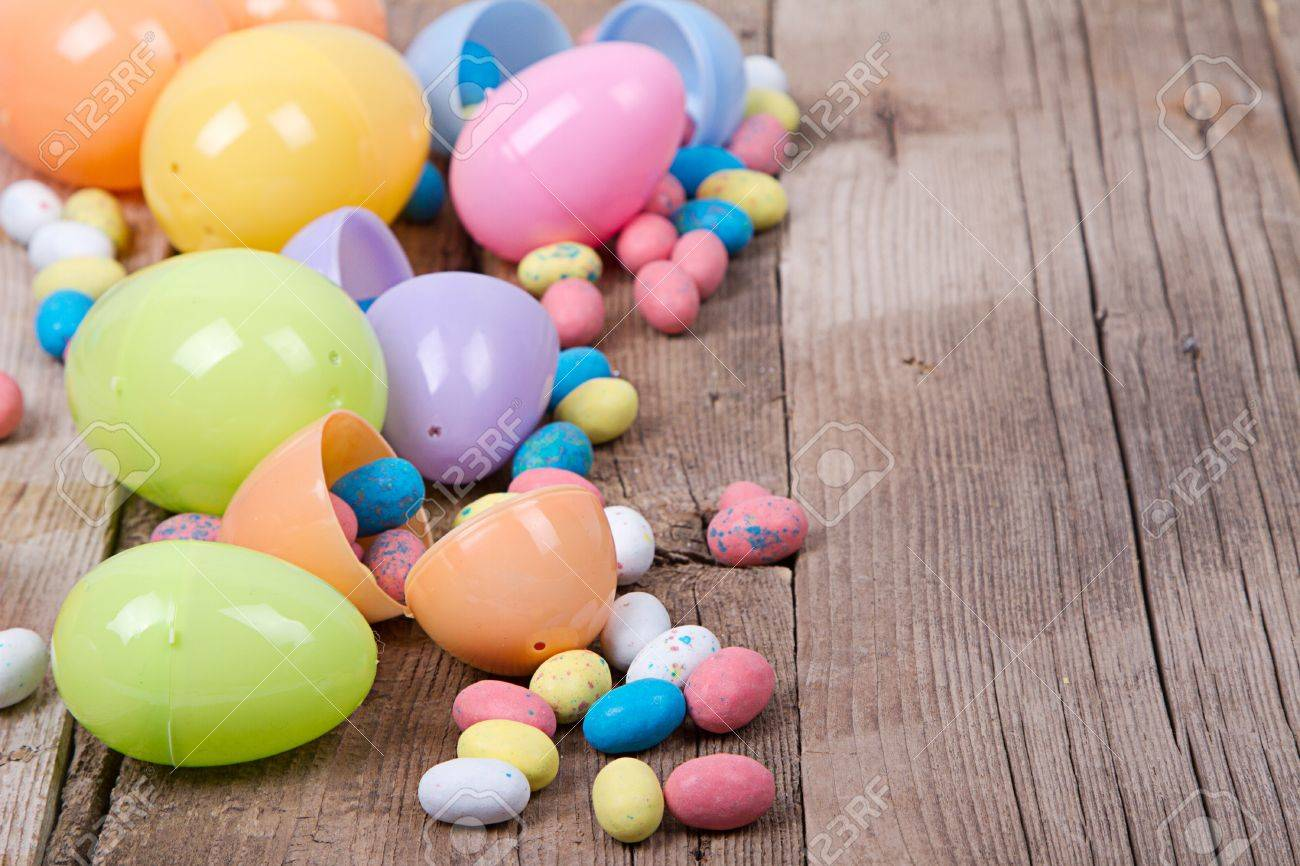 Plastic Easter Eggs Filled With Candy On A Wooden Background Stock Photo