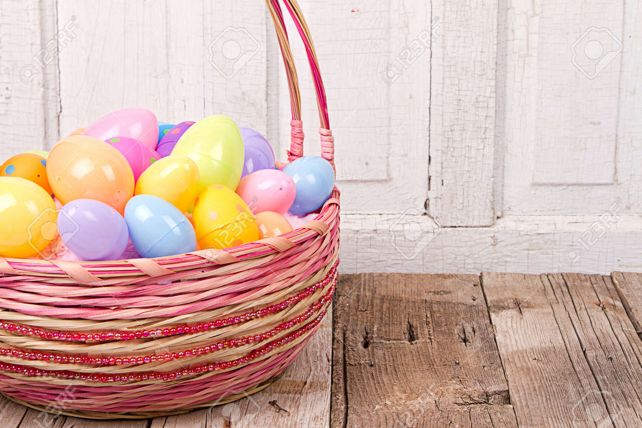 Plastic Easter Eggs In Basket On Rustic Wooden Background Stock Photo