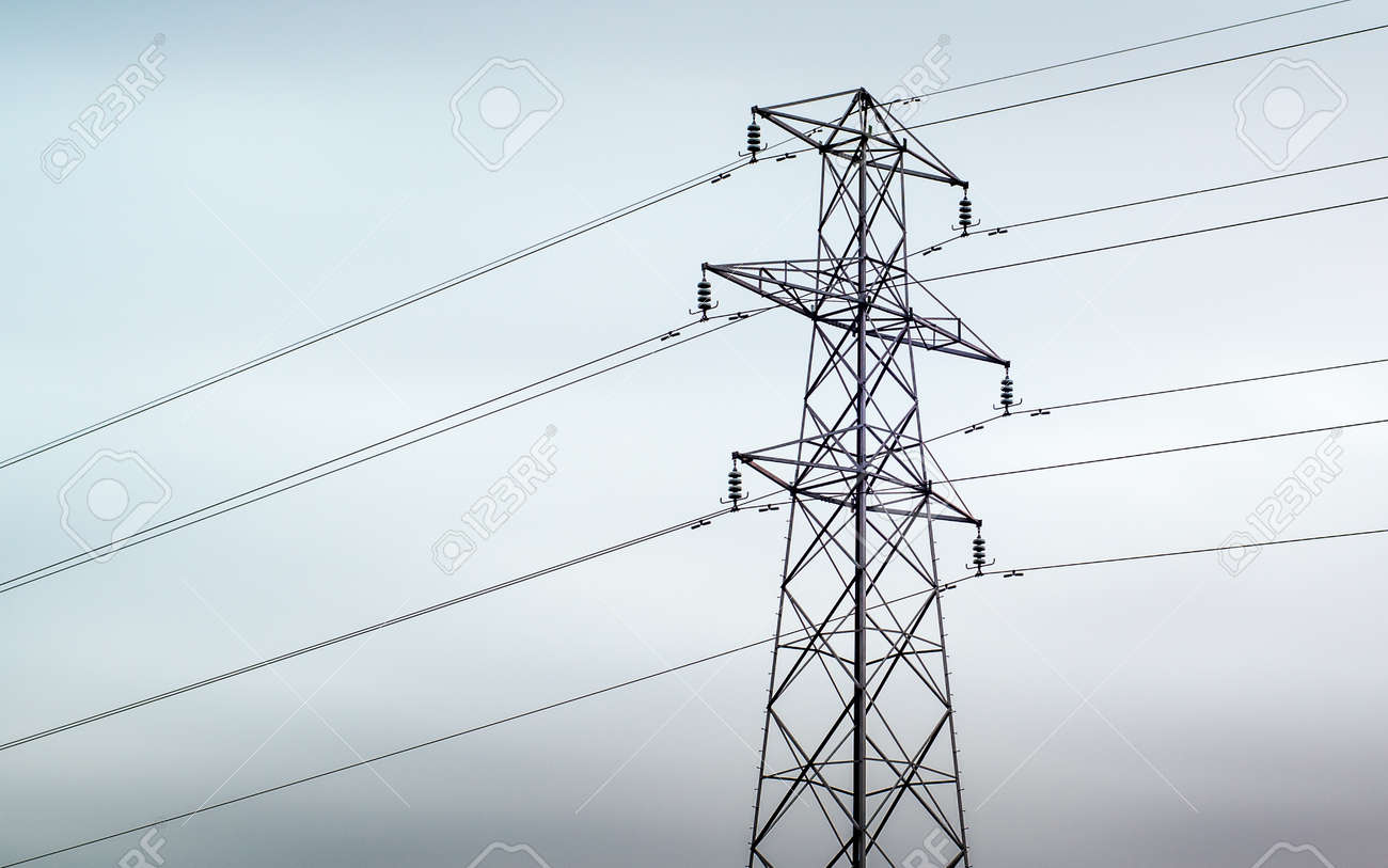 An electrical pylon against a grey overcast sky in the UK - 120891960