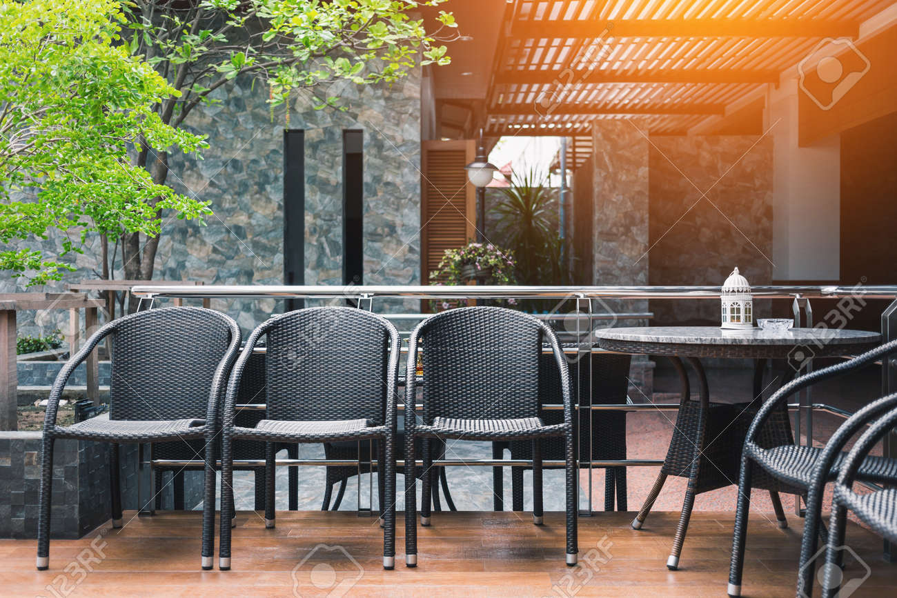 Rincón De Fumadores Decorado Con Muebles Negros En La Terraza Del Piso De Madera Con Suave Luz Naranja Del Techo