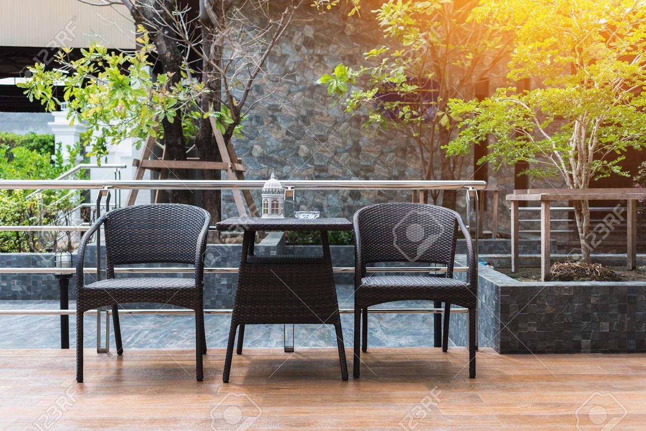 Rincón De Fumar Decorado Con Muebles Negros En La Terraza Del Piso De Madera Con Suave Luz Naranja