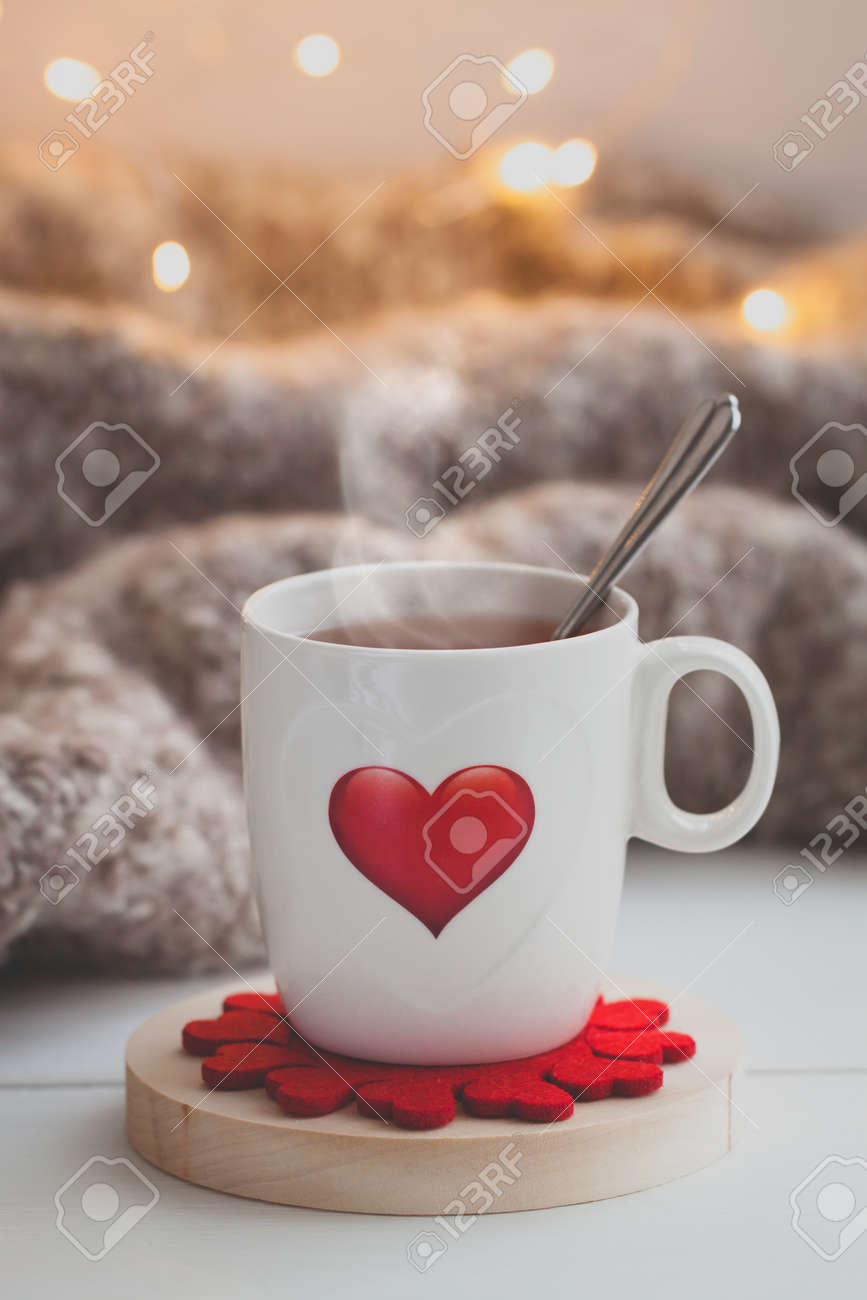 festive cup of tea with a smoke and a red heart over the knitted