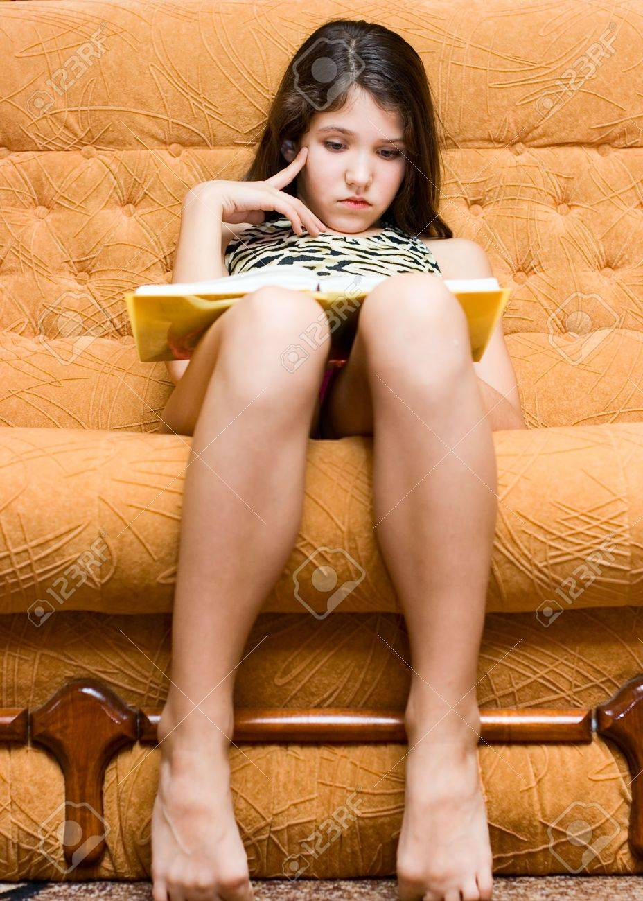 Teen girl reading book on sofa Stock Photo - 6453690