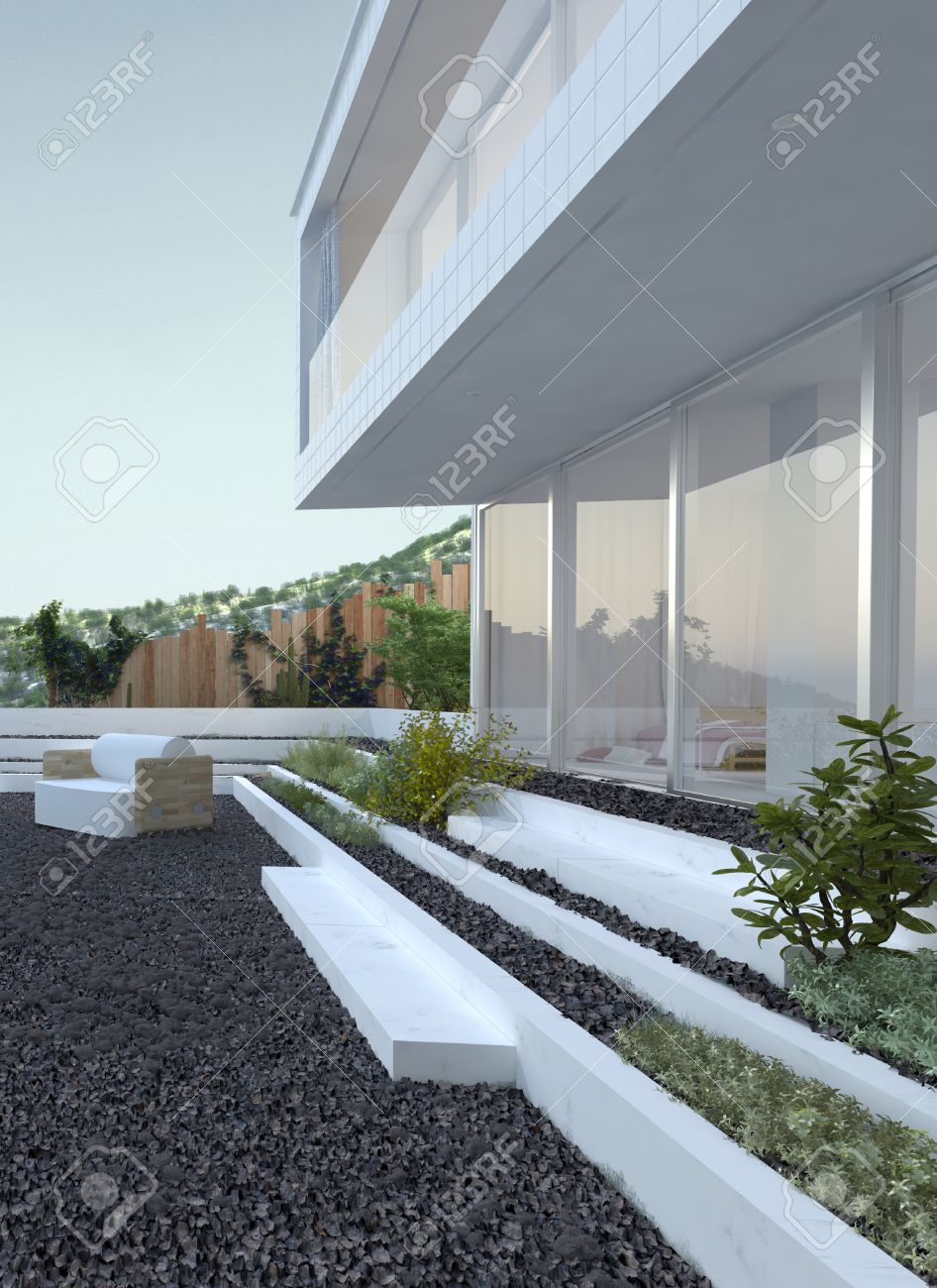 pebble patio with a comfortable armchair in front of a modern house with large glass windows