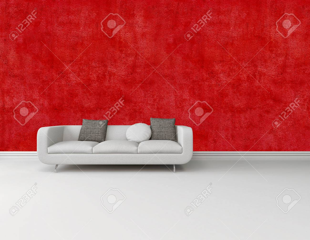 Modern White Sofa With Grey Cushions Against A Bright Red Wall On A White  Floor With