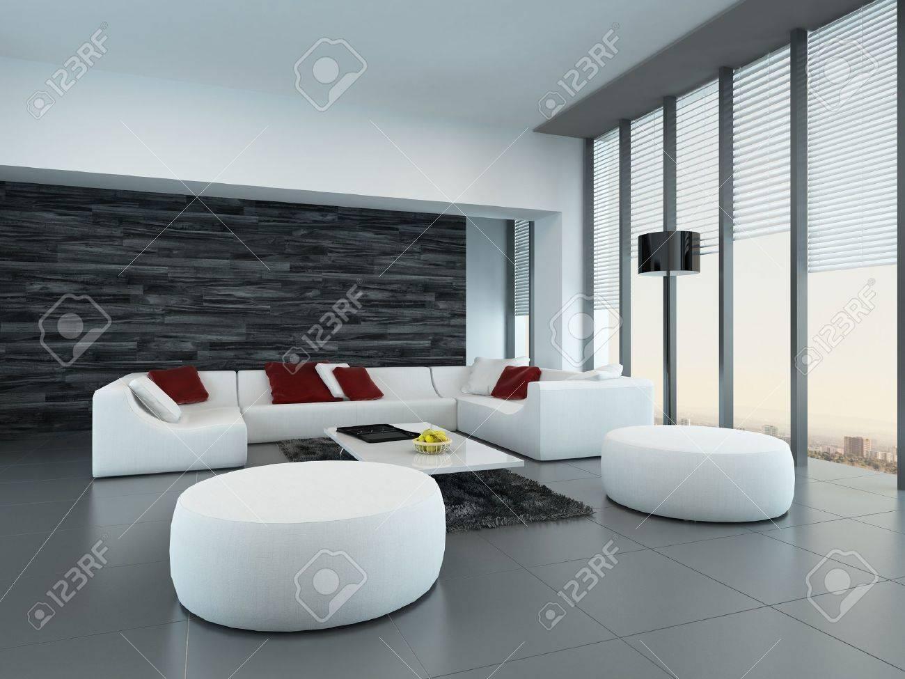 Perspective inclinée d\'un gris et blanc salon moderne intérieur avec des  poufs et un grand canapé en face des fenêtres du sol au plafond de verre ...