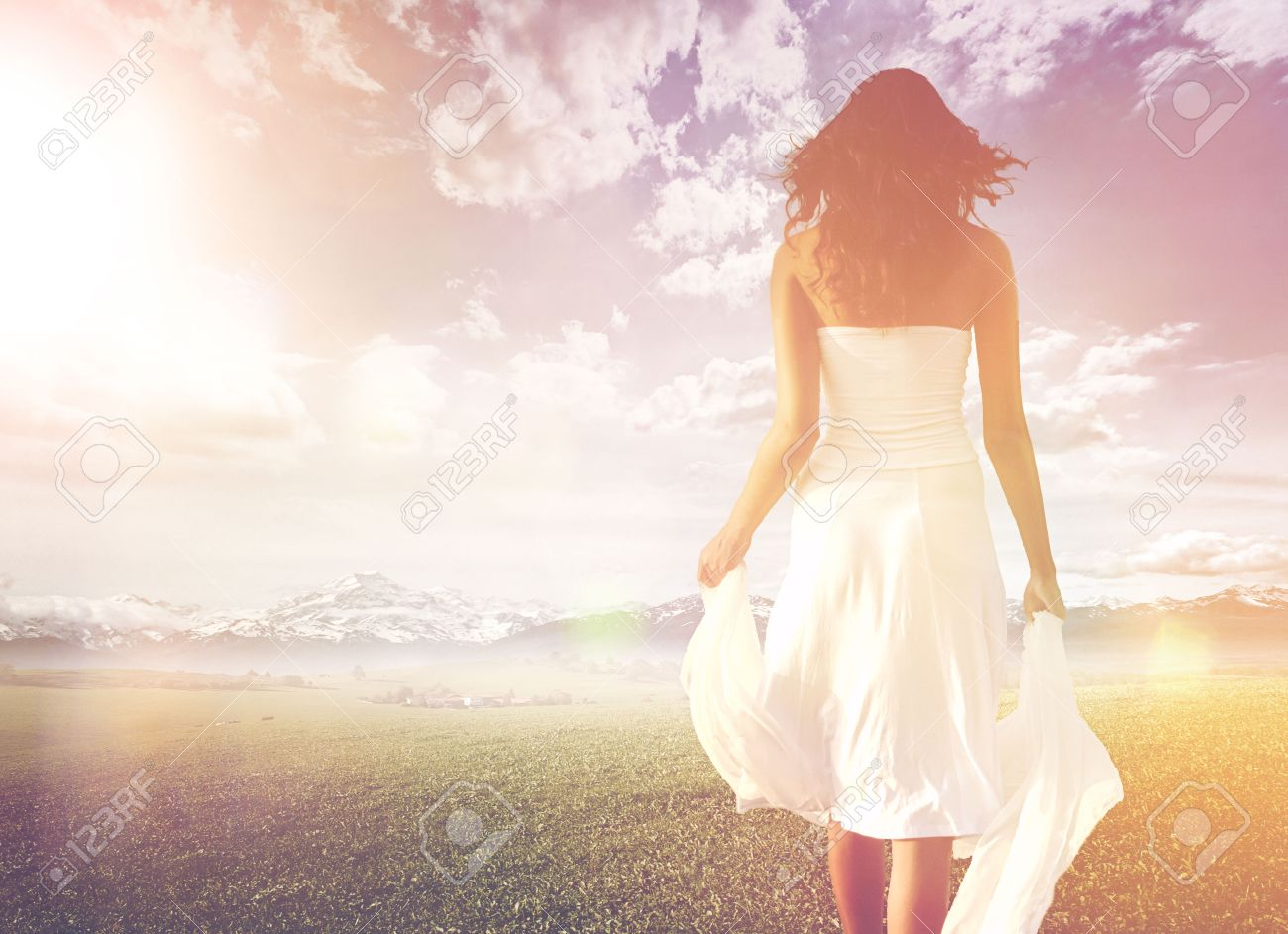 Slender long-haired woman wearing white summer dress while walking on a green meadow towards a bright and sunny horizon, under a dramatic sky, shot from behind, in high-key - 30007583