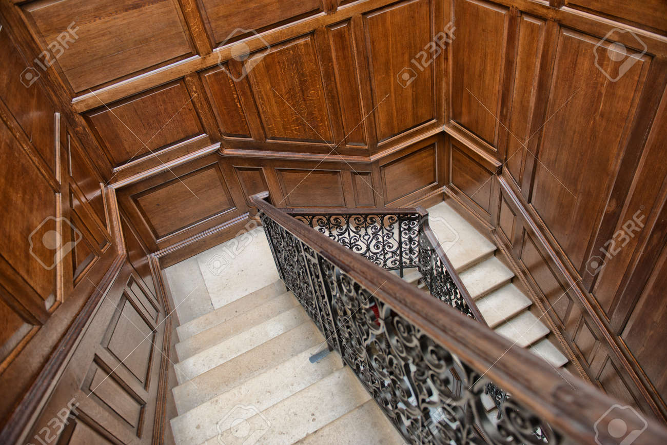 Stock Photo - Winding interior staircase with wood paneling on the walls  and an ornate wrought iron and oak bannister viewed looking down the treads  from ... - Winding Interior Staircase With Wood Paneling On The Walls And