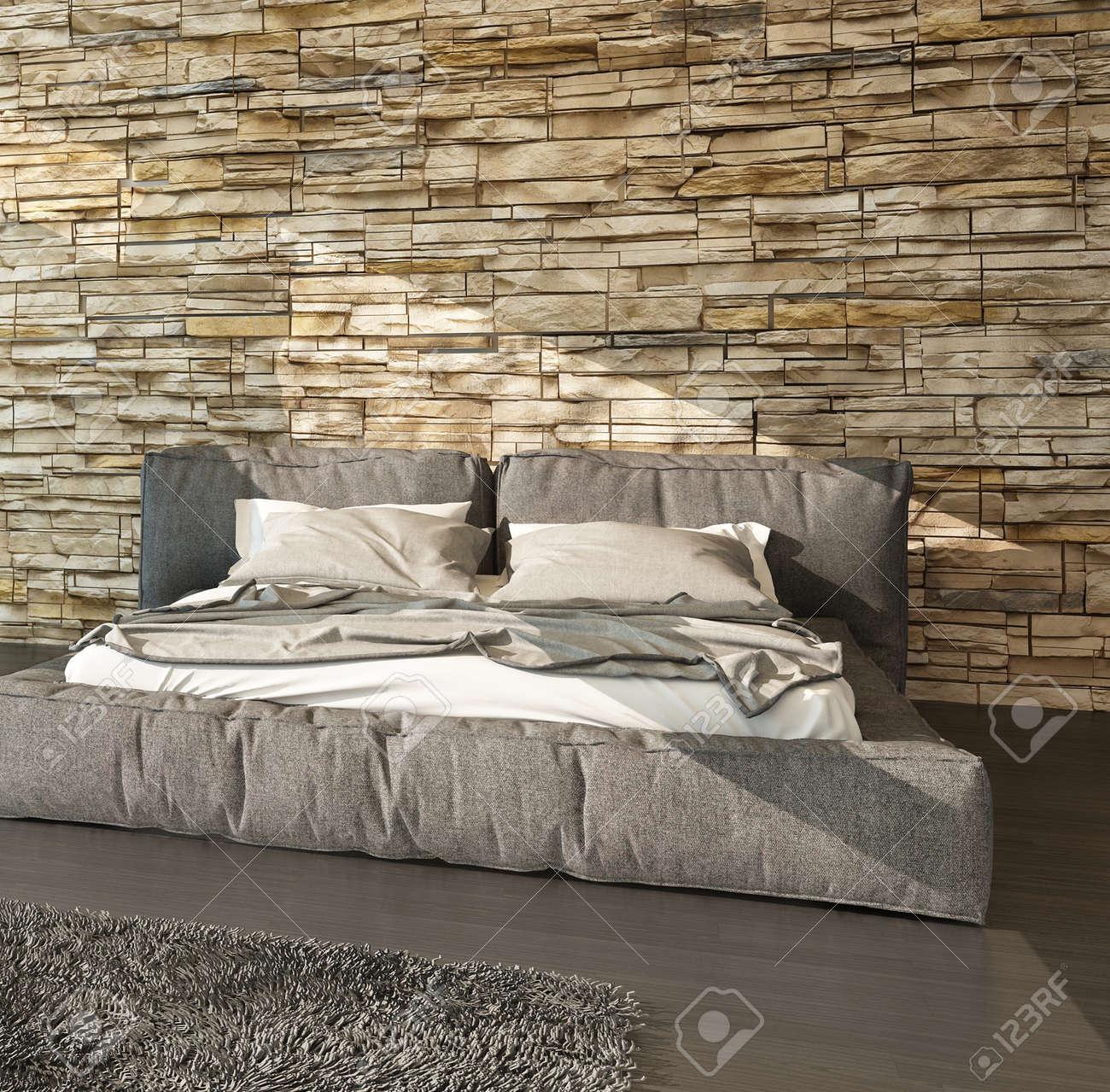 Lit moderne avec tête de lit rembourrée rembourrée et de pied dans les tons  de brun contre un mur texturé finition pierre brute dans un intérieur de ...
