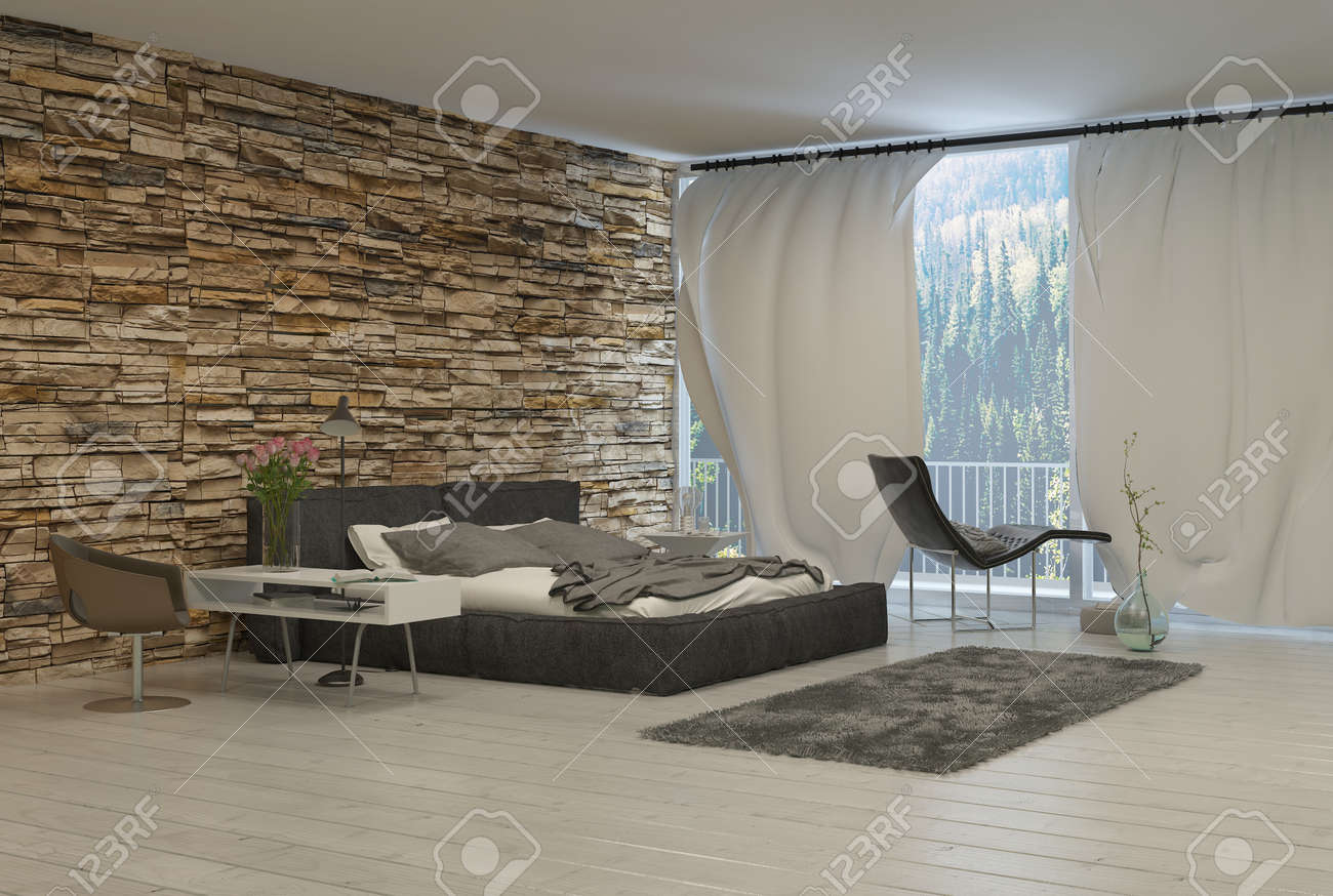 Bedroom With Modern Furnishings And Exposed Brick Wall And View Of Forest  From Balcony Stock Photo