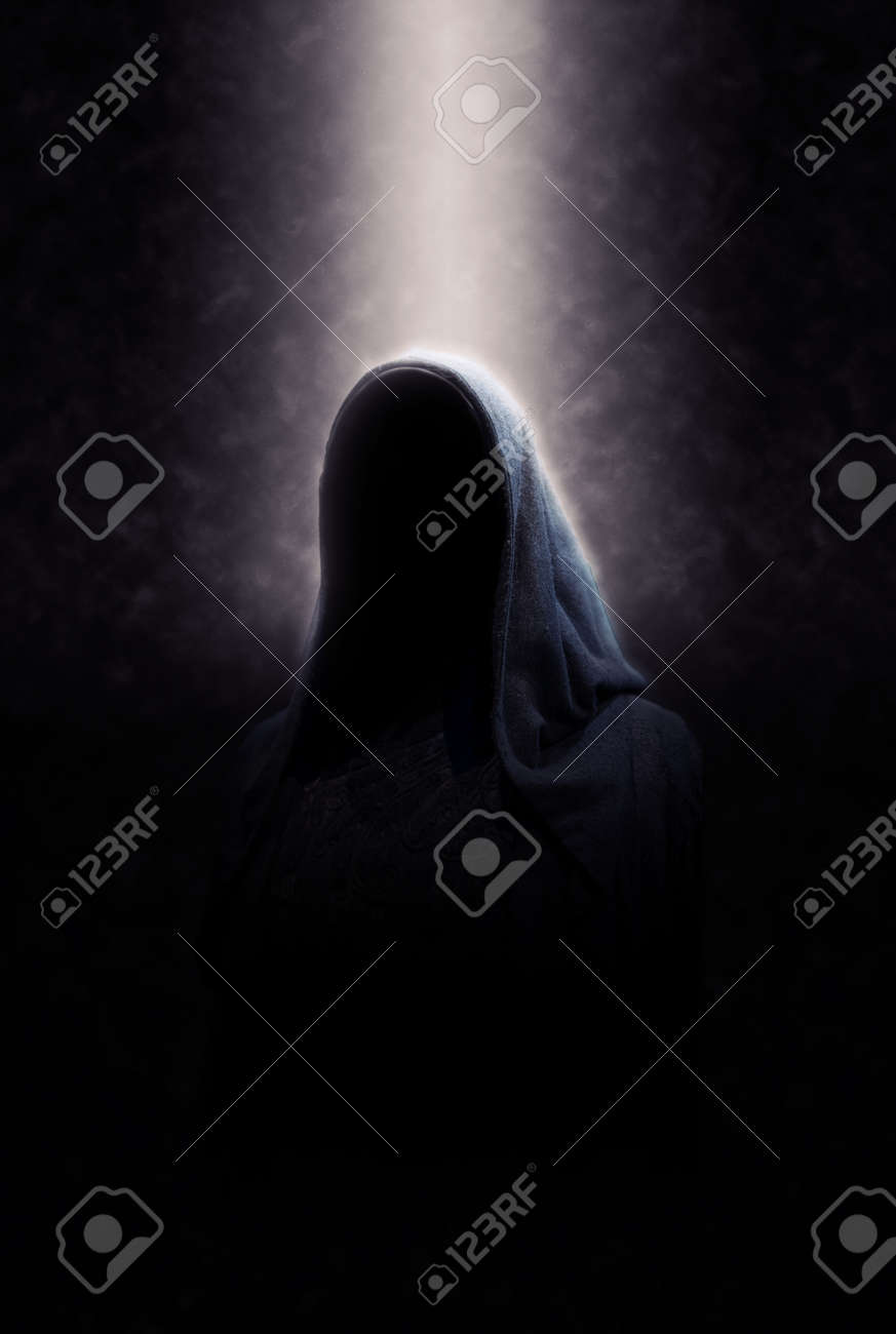 Eerie Image of Creepy Dimly Lit Faceless Cloaked Figure in Spotlight on Dark Background - 38437454