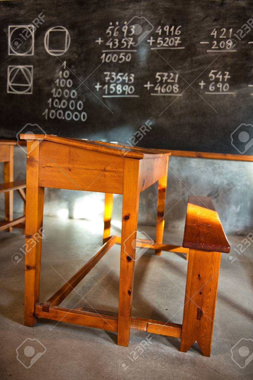 Old fashioned rustic school room with wooden student desks and..