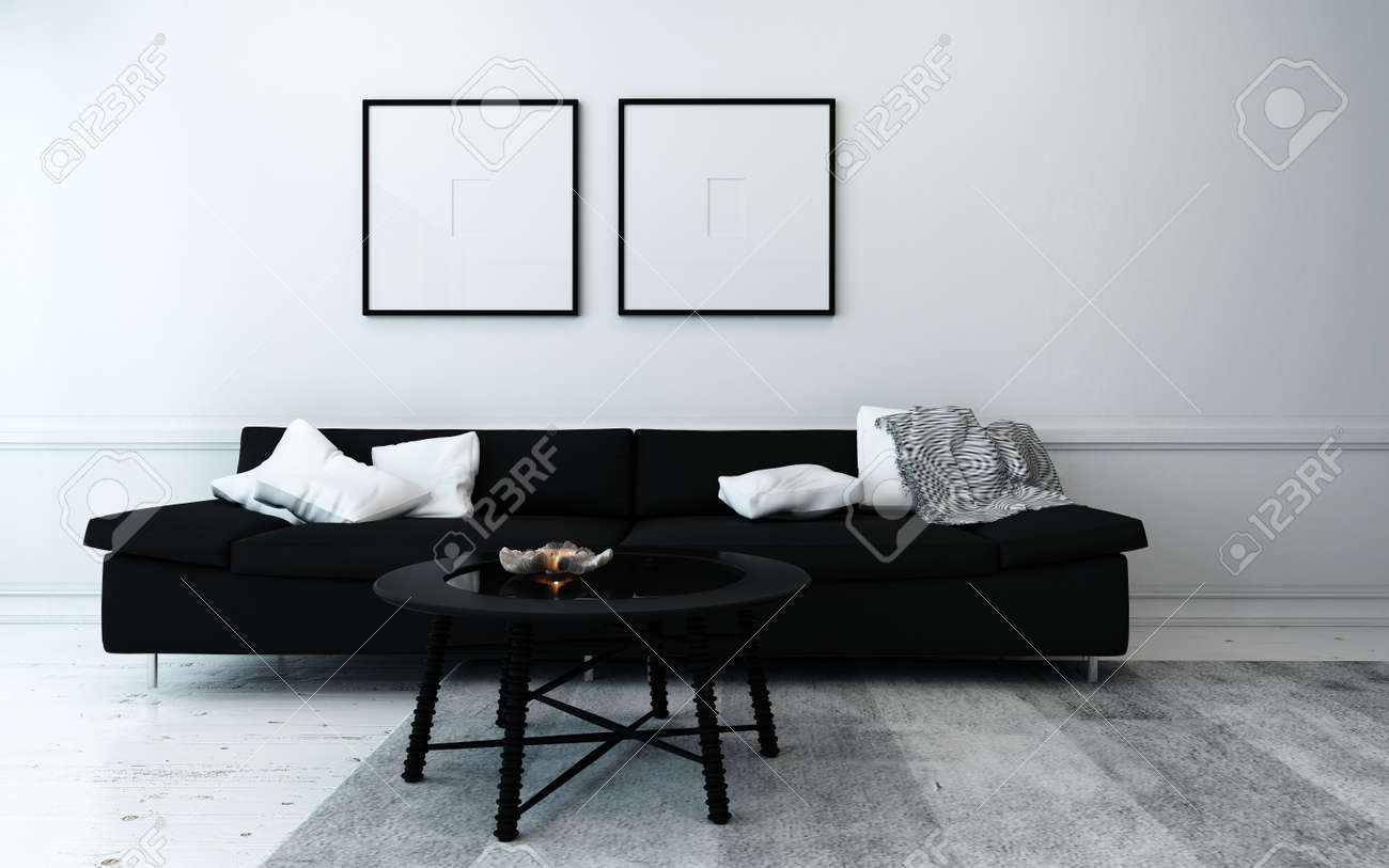 sparsely decorated modern living room with black sofa coffee table and artwork hanging on