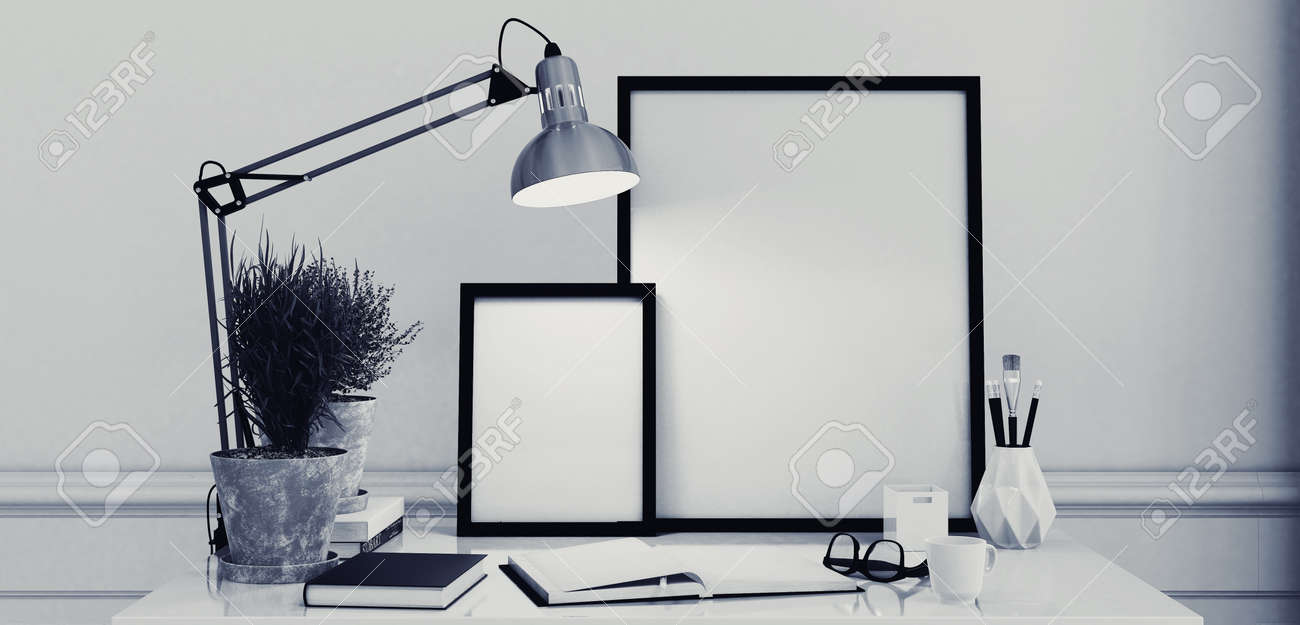 Blank picture frames on a simple modern desk or writing table with an open journal and anglepoise lamp in monochromatic black and white decor, 3d rendering Standard-Bild - 52465037