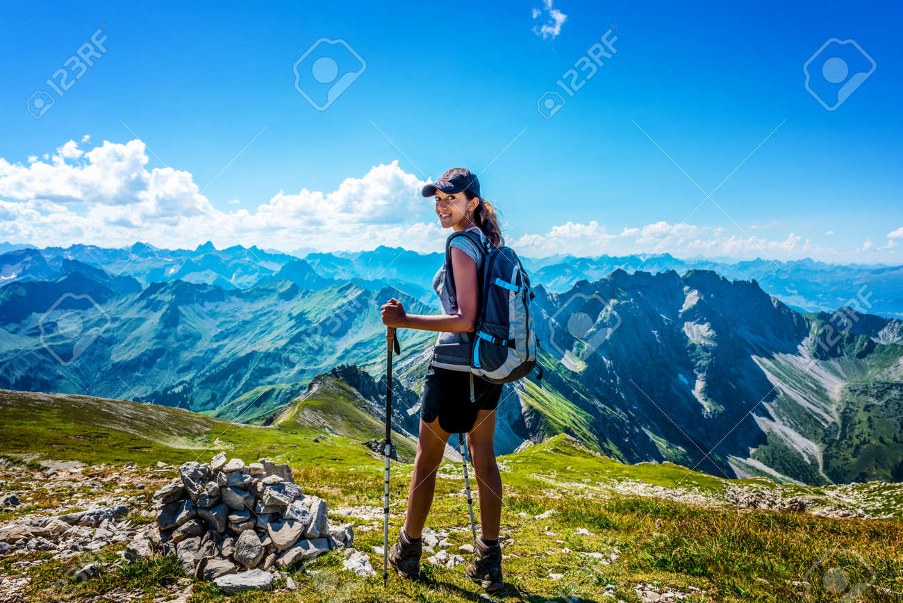 Happy young woman in hiking gear looking back as she stands before the vast mountain range of the Allgau Alps Standard-Bild - 62734417