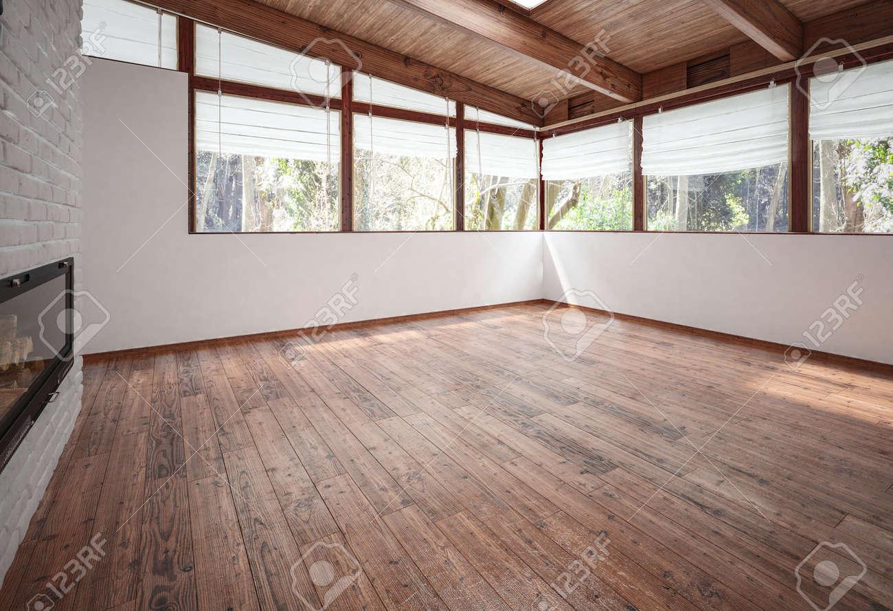 Leere Wohnzimmer Mit Kamin, Holzboden Und Decke Mit Balken Und ...