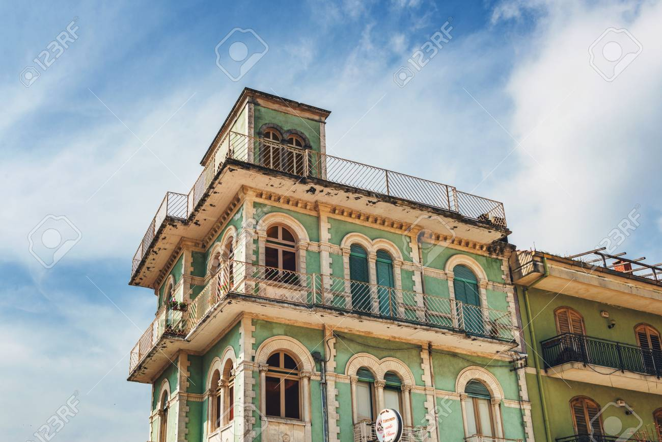 Top Of Old Green Multistorey Building With Balconies And Flat