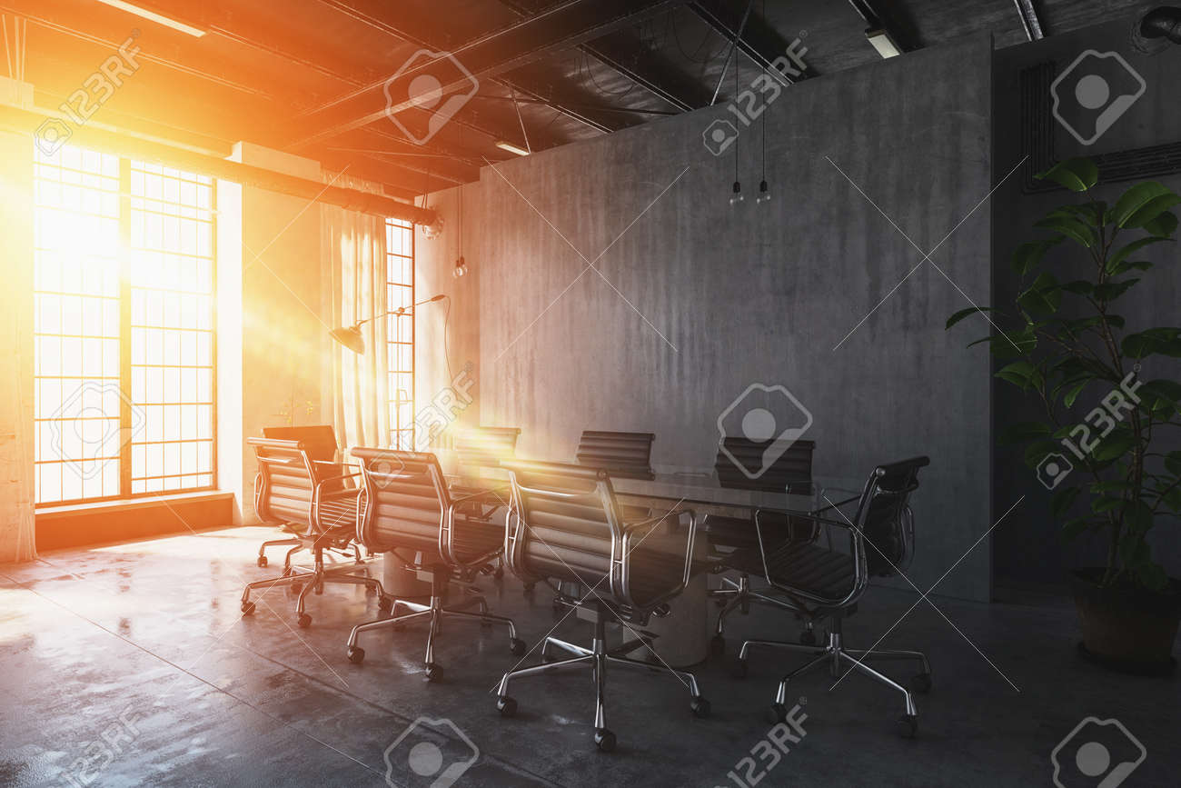 Bright Warm Sunset Light Streaming Through Windows Into An Industrial Style Office With Table And