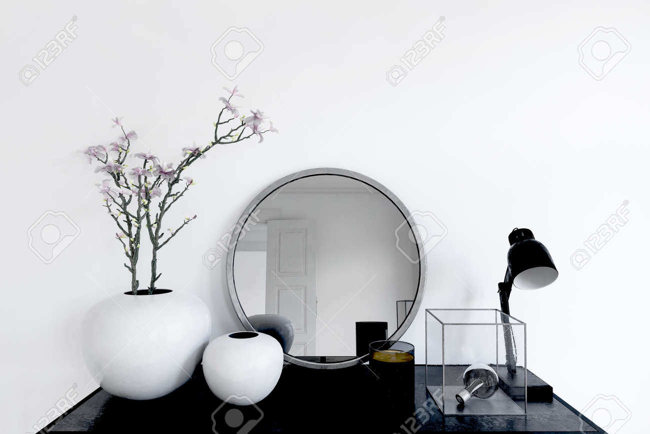 Close up on mirror and plant pots next to lamp and metal trinket in transparent box on modern black table. 3d rendering - 130167322