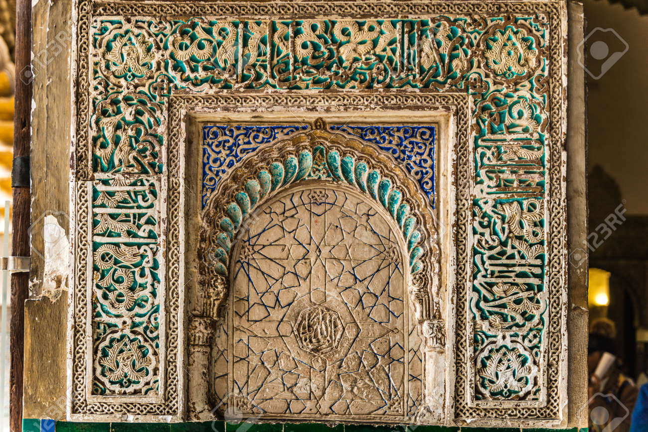 SEVILLE, SPAIN - December 09 2019: Detail of an ornate carved tiled panel in the Real Alcazar palace in Seville, Spain a popular tourist attraction and Unesco listed site - 144093566