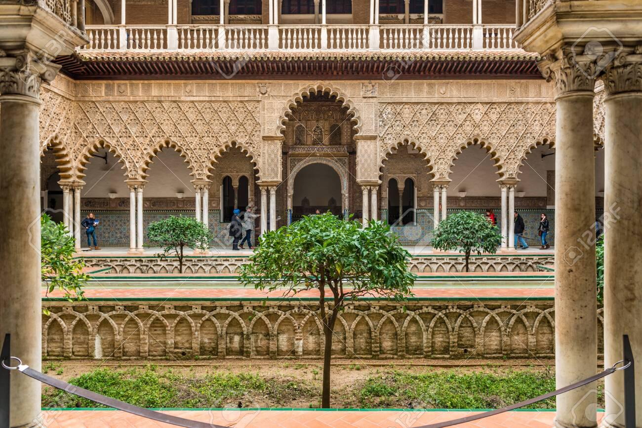 SEVILLE, SPAIN - December 09 2019: Patio de las Doncellas courtyard, Real Alcazar, Seville Spain viewed between columns, a Unesco World Heritage Site - 144093569