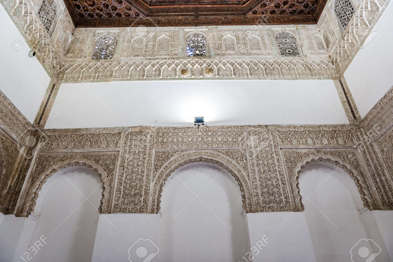 SEVILLE, SPAIN - December 09 2019: White walls with ornamented arches inside the famous Spanish palace of royal Alcazars of Seville - 144093571
