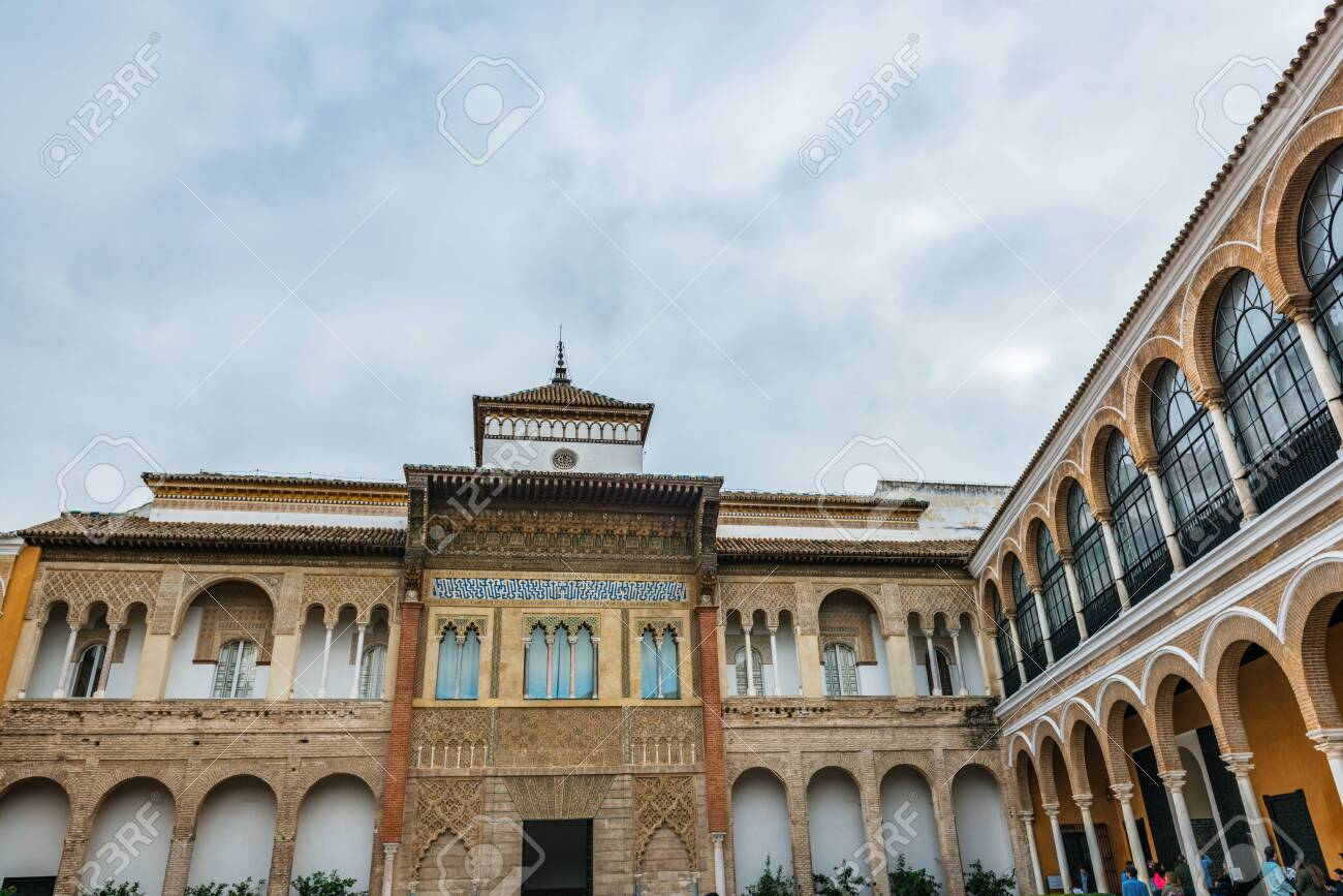SEVILLE, SPAIN - December 09 2019: Upper floor of Patio de la Monteria courtyard with its arched windows in the Real Alcazar, a Spanish Royal Residence in Seville - 144093584