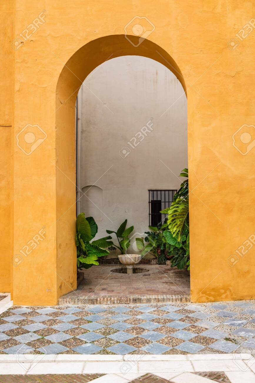 SEVILLE, SPAIN - December 09 2019: Arch leading through a colorful orange wall to enclosed courtyard garden with green plants and small water feature in Real Alcazar, Seville, Spain - 144093585