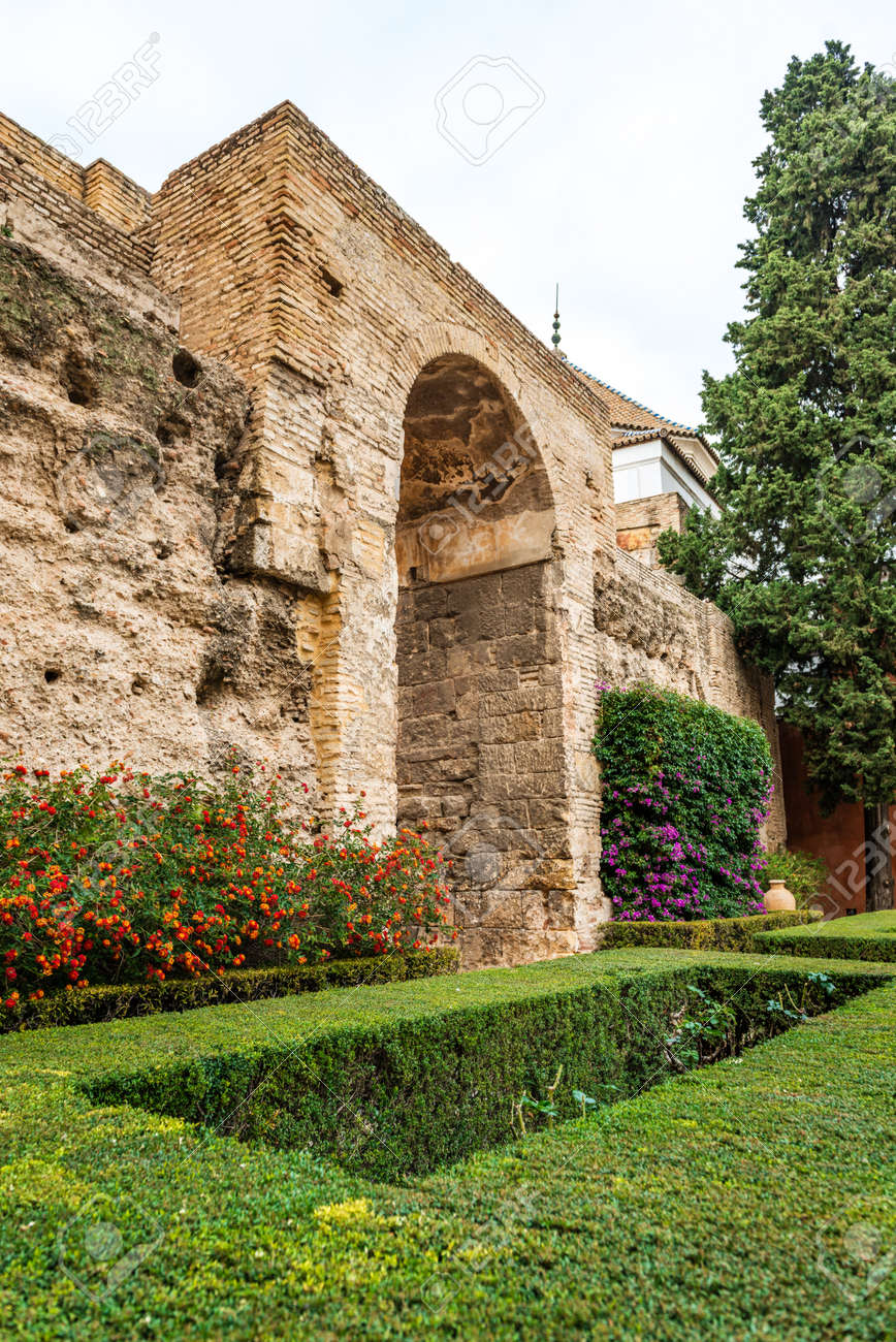 SEVILLE, SPAIN - December 09 2019: Garden with colorful flowering plants and neat green lawn and massive stone wall at Real Alcazar royal palace in Seville, Spain a popular tourist attraction - 144093588