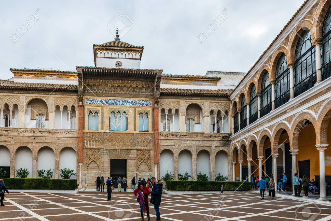 SEVILLE, SPAIN - December 09 2019: Tourists sightseeing in the Real Alcazar, Seville, Spain in the Patio de la Monteria courtyard under a cloudy sky - 144093589