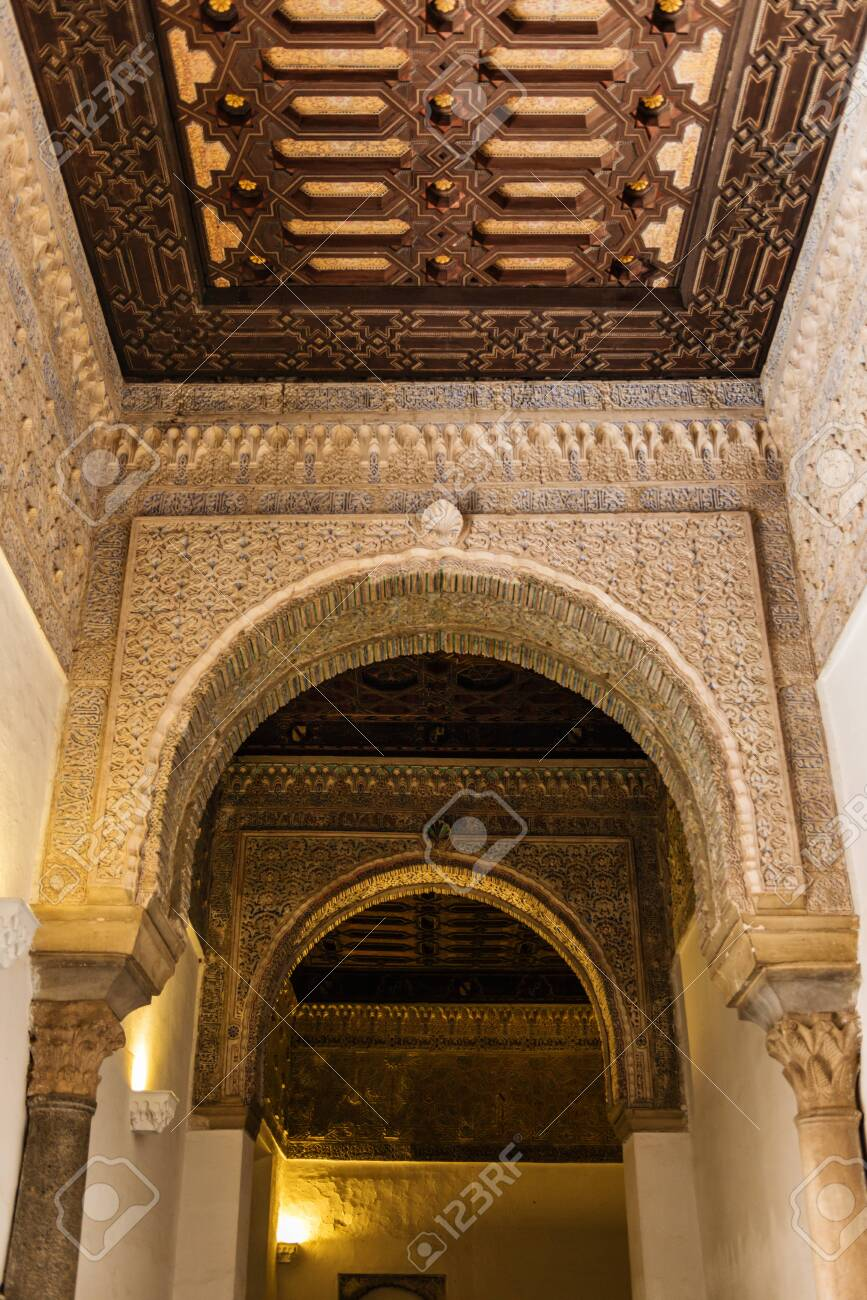 SEVILLE, SPAIN - December 09 2019: Ornamented arches and ceiling of the corridor inside the Royal Alcazars of Seville castle in Spain. Famous Andalusian architecture - 144093591