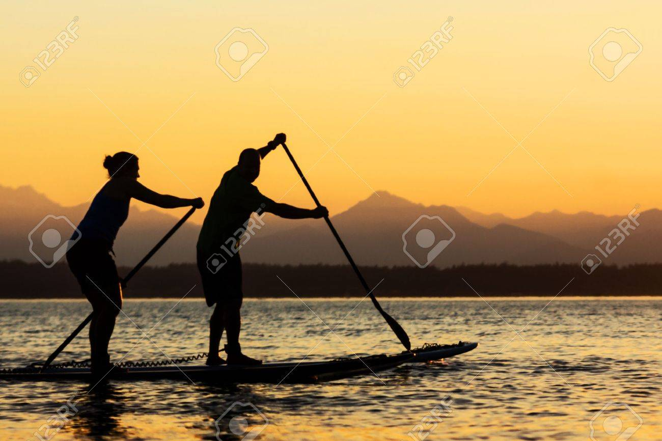 Couple paddling stand up paddle boards - 15325571