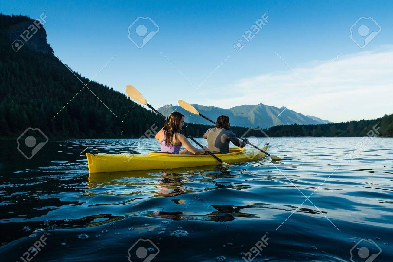Couple paddling in kayak on lake. - 15783086
