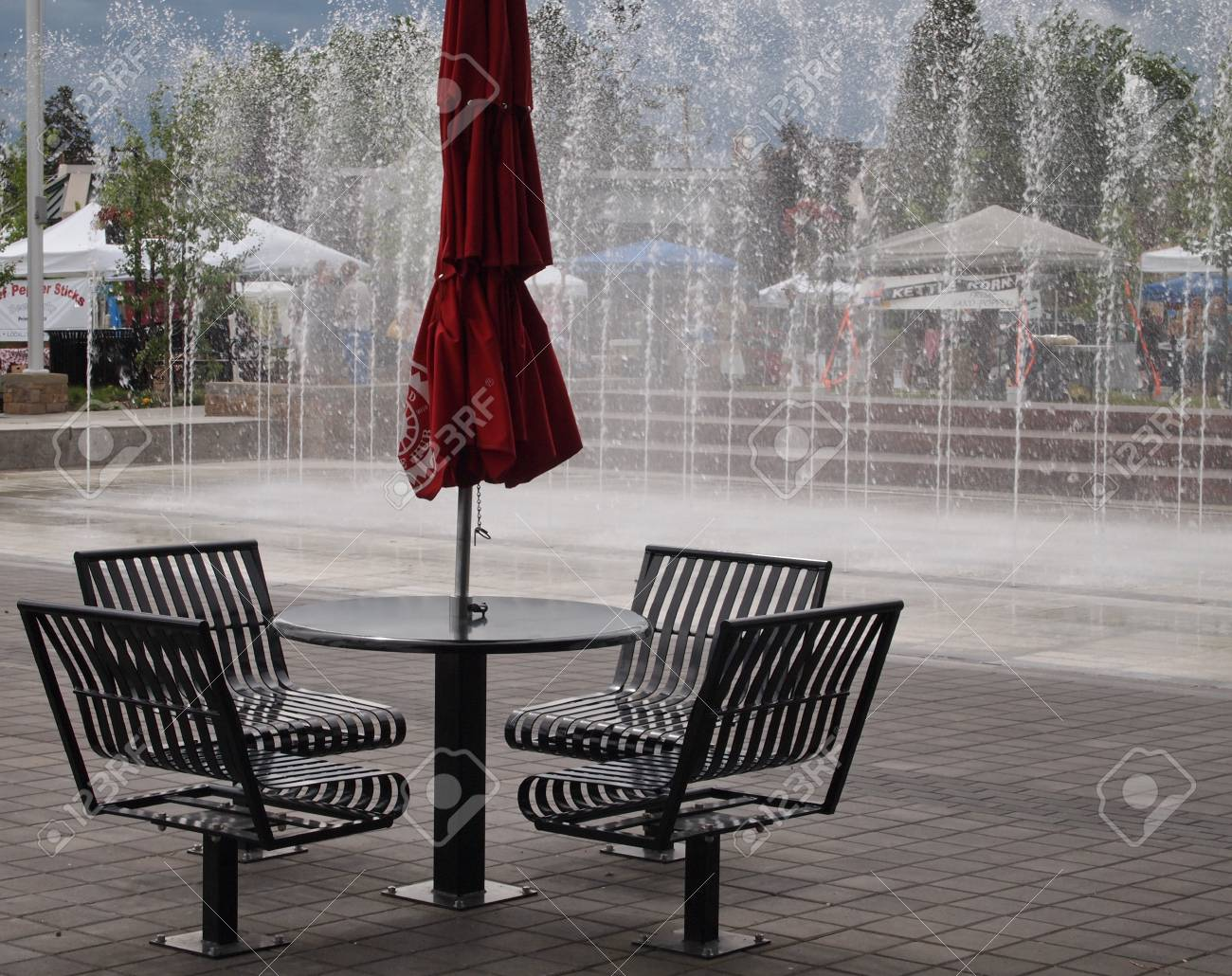 An Outdoor Cafe Style Table And Chairs With A Fountain In The - Outdoor cafe style table and chairs